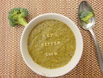 Get better soon written in vegetable soup with spoon. And vegetable next to it royalty free stock photography