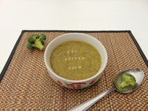 Get better soon written in vegetable soup with spoon. And vegetable next to it Royalty Free Stock Photo