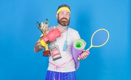 Get body ready for summer. Man bearded athlete hold sport equipment jump rope fitness mat boxing glove expander racket. And golden goblet. Choose sport you like royalty free stock image