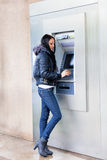 Get cash from an ATM. Girl get cash from an ATM on a city street Stock Photos