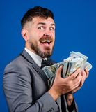 Get cash easy and quickly. Cash transaction business. Man happy winner rich hold pile of dollar banknotes blue. Background. Easy cash loans. Businessman got royalty free stock photo