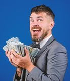 Get cash easy and quickly. Cash transaction business. Man happy winner rich hold pile of dollar banknotes blue. Background. Easy cash loans. Businessman got royalty free stock image