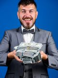 Get cash easy and quickly. Cash transaction business. Man happy winner rich hold pile of dollar banknotes blue. Background. Win lottery concept. Easy cash loans stock photos