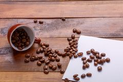 Get enough sleep from a mug grain coffee. coffee grains get out of the cup over paper and wooden background. Place for text Royalty Free Stock Image