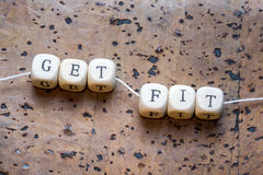 Get fit. Text written on wood block on a brown cork background royalty free stock image