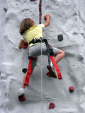 Get a Grip. Young girl scaling a rock climbing wall Stock Photography