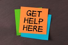 Get Help Here. 'Get Help Here' colorful notes pasted on blackboard Royalty Free Stock Photo