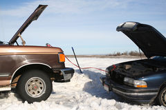 Get a Jump Start. Two Vehicles in Snow after winter blizzard, one getting jump started by the other stock photography