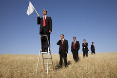 Get in line to fail. A group of businessman in the field getting in line for there time to surrendering stock images