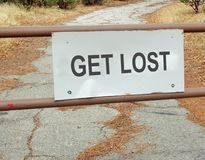Get Lost Road Sign. This is an image of a gate with a very unwelcoming sign that says `Get Lost`. The background is a rural road. The image could be used to royalty free stock image