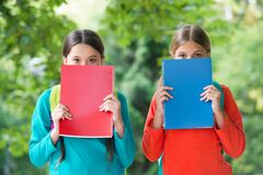 Get more knowledge. Little children cover faces with books. Small bookworms. Library books. Fiction and non-fiction