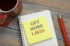Get More Likes concept. Notebook page with text, red pencil and coffee cup. Office desk table top view Royalty Free Stock Images