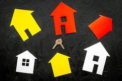 Get a mortgage. House silhouette near apartment keys on black background top view royalty free stock photo