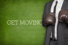 Get moving on blackboard with businessman on side. Get moving on blackboard with businessman wearing boxing gloves Royalty Free Stock Photo