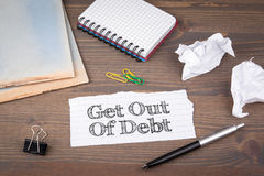 Get Out of Debt. paper sheet from the booklet on the wooden table Stock Image
