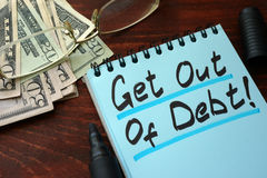 Get out of Debt. Get out of Debt written on a notepad with marker Stock Photography