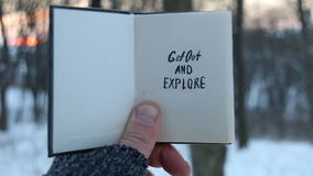 Get out and explore text. Travel idea. Book and text. Get out and explore. Hand holding a book with the inscription stock video