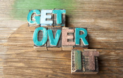 Get Over It - Wooden typeset word concept. Get Over It  in multicolor wooden letterpress letter printing blocks with retro camera lens Royalty Free Stock Photos