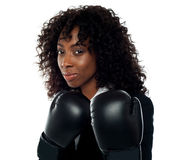Get ready for some action. Beautiful female executive wearing boxing gloves. Get ready for some action Stock Image