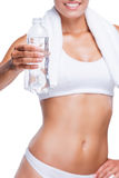 Get refreshed!. Close-up of beautiful young woman in white bra and panties holding bottle with water while standing isolated on white Stock Images