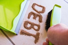 Get Rid of Debt Concept. With debt written in dirt on a floor and a person is about to sweep the debt dirt in a dust pan using a small hand broom Royalty Free Stock Photography