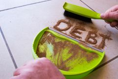 Get Rid of Debt. With debt written in dirt on a floor and a person is about to sweep the debt dirt in a dust pan using a small hand broom stock images