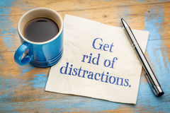Get rid of distractions advice or reminder. Handwriting on a napkin with a cup of espresso coffee Stock Images