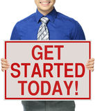 Get Started Today. A man holding a sign indicating Get Started Today royalty free stock photography