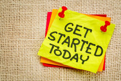 Get started today reminder note. Get started today reminder - handwriting on a sticky note against burlap canvas stock photo