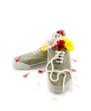 Get the Stink Out. A contradiction concept. A pair of stinky sneakers with fragrant flowers in them royalty free stock photography