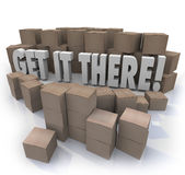 Get It There Shipping Cardboard Boxes Fast Shipment. Get It There words surrounded by shipment cardboard boxes to illustrate the importance of getting important Stock Photography