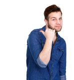 Get to the back. Portrait of a young man with frown showing thumb pointing behind on isolated white background Stock Photography