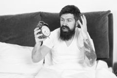 Get up with alarm clock. Overslept again. Tips for waking up early. Tips for becoming an early riser. Man bearded. Hipster sleepy face in bed with alarm clock royalty free stock images