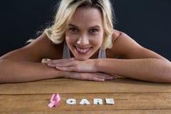 Get a vérifié le texte et la main tenant la carte avec les femmes roses de conscience de cancer du sein Photographie stock libre de droits
