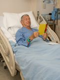 Get Well. Man in hospital bed reading a get well card Royalty Free Stock Photo