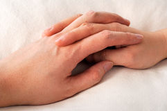 Get well soon. Holding hands with fingers crossed in bed - caring Royalty Free Stock Images