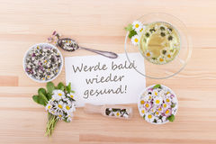 Get well soon!. Card for recovery with tea and daisies and German text: Get well soon royalty free stock images
