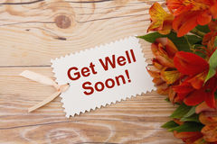 Get Well Soon Gift Tag with Flowers. Some lilies on weathered wood with a gift tag with text Get Well Soon royalty free stock images