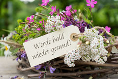 Get well soon. Greeting card with colorful bouquet and german text: Get better soon stock image