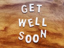 Get Well Soon Message on Wooden Table. High Angle View of Get Well Soon Message on Wooden Table royalty free stock photos