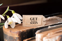 Get well soon. Snowdrop and card with lettering get well soon stock photography