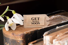 Get well soon. Snowdrop and card with lettering get well soon stock photos
