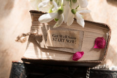 Get well soon. Get well soon! Start now! Text, wooden background, book and snowdrops stock images