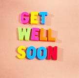 Get well soon. Text 'get well soon' in colorful uppercase letters on beige background royalty free stock photo
