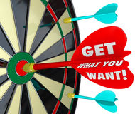 Get What You Want Words Dart Board Target. Get What You Want words on a dart board and a direct hit to illustrate a winning competitor in a game to achieve your Stock Photography