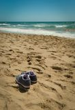 Get your shoes off, we are in the beach!!. Summer view, a pair of shoes  on the sand. With the beach in the background Stock Photography