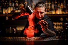 Getatoeeerde barman die kruidenpoeder toevoegen in wi van een cocktailglas royalty-vrije stock afbeeldingen