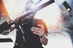 Getatoeeerde spier mannelijke holdings mobiele telefoon in handen en het gebruiken van kaart app voor het voorbereiden van de rou royalty-vrije stock foto