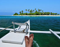 The Getaway. Tanned person riding on a boat going to a beautiful tropical island Royalty Free Stock Image