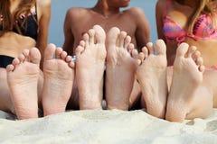 Getaway. Soles of teenagers sunbathing on sandy beach Stock Photo